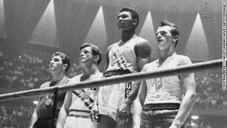 The winners of the 1960 Olympic medals for light heavyweight boxing on the podium at Rome: Cassius Clay,  Zbigniew Pietrzykowski of Poland, Giulio Saraudi (Italy) and Anthony Madigan (Australia).