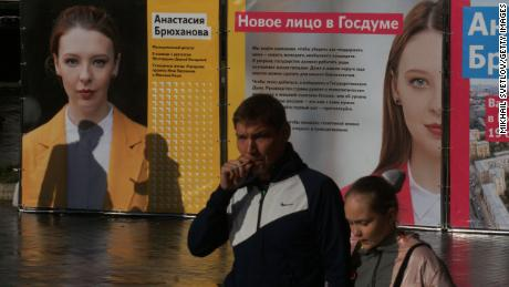 People walk past posters of Anastasia Bryukhanova, an independent candidate for the State Duma poll, on September 5.