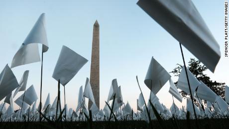 & quot;  Na América: Lembre-se de & quot;  Uma instalação de arte pública em Washington, D.C., em homenagem a todos os americanos que morreram de Covid-19.  Em 18 de setembro, havia mais de 660.000 pequenas bandeiras de plástico no local, algumas com mensagens pessoais para os mortos.