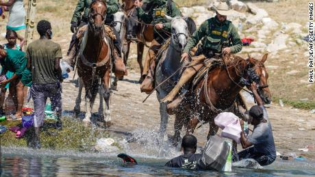 United States Border Patrol agents on horseback tries to stop Haitian migrants from entering an encampment on the banks of the Rio Grande near the Acuna Del Rio International Bridge in Del Rio, Texas on September 19, 2021. - The United States said Saturday it would ramp up deportation flights for thousands of migrants who flooded into the Texas border city of Del Rio, as authorities scramble to alleviate a burgeoning crisis for President Joe Biden's administration. (Photo by PAUL RATJE / AFP) (Photo by PAUL RATJE/AFP via Getty Images)
