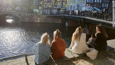 Some folks sit in the sun on a canal in Amsterdam. The Dutch treasure their niksen — or do nothing time.