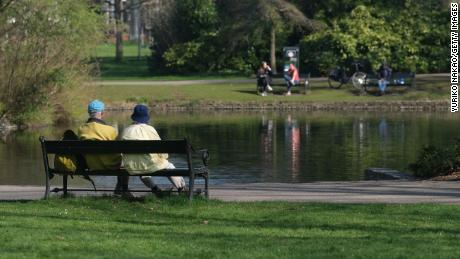 The ultimate niksen: A couple sits on a bench in front of a pond at Wilhelminapark in Utrecht, Netherlands.