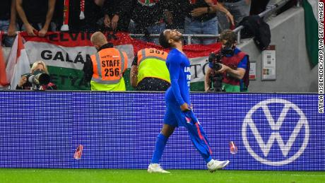 Hungary's fans react throwing cups of beer at England forward Raheem Sterling.