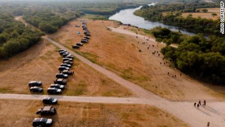 Texas governor approves miles-long steel barrier of police vehicles to deter the more than 8,000 migrants in Del Rio
