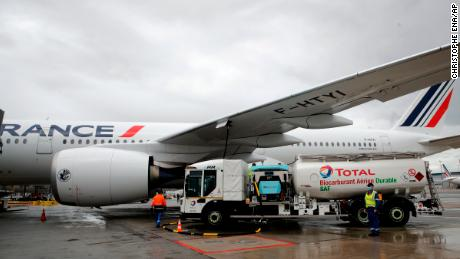 Workers refuel an Airbus A350 with sustainable aviation fuel at Roissy airport, north of Paris, on May 18, 2021.