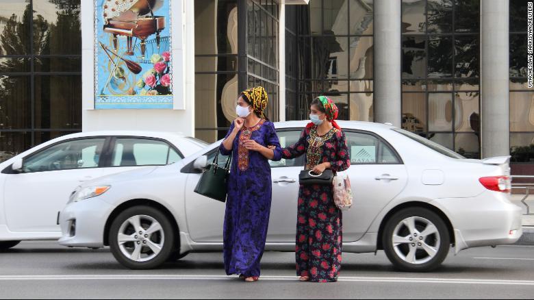 Women wearing protective face masks cross a road in Ashgabat, Turkmenistan, on July 15, 2020.