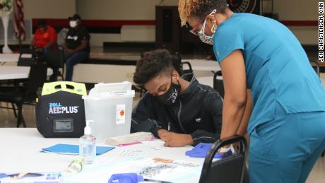 At a teen-focused Covid-19 vaccine clinic, 15-year-old Raymond Slaughter fills out his paperwork before getting his first shot.