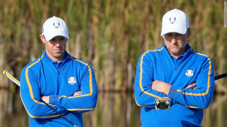 Team Europe's Rory McIlroy and Ian Poulter wait to putt on the fifth hole.