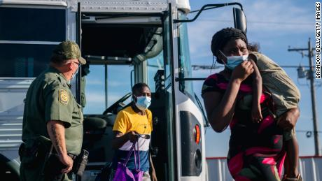 Migrants exit a Border Patrol bus and prepare to be received by the Val Verde Humanitarian Coalition after crossing the Rio Grande on September 22, in Del Rio, Texas.