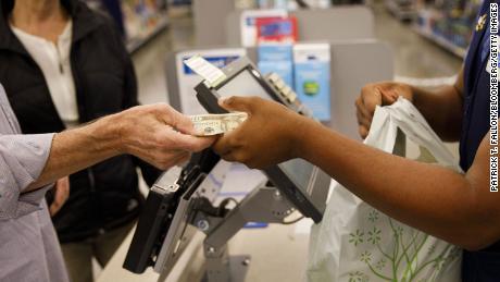 Клиент передает наличные сотруднику при совершении покупки в магазине Walmart в Бербанке, штат Калифорния, 16 ноября 2017 года.