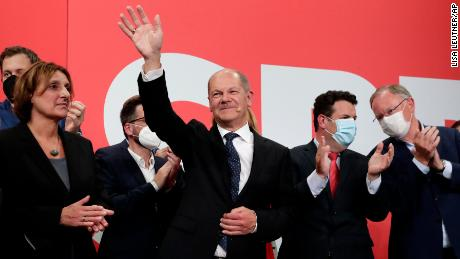 SPD's Olaf Scholz waves to his supporters after German parliament election at the party's headquarters in Berlin, on September 26.