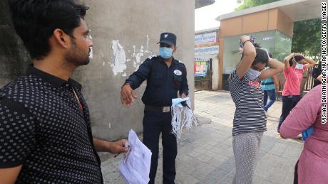 Les candidats reçoivent de nouveaux masques jetables alors qu'ils se préparent à passer l'examen d'éligibilité du Rajasthan pour les enseignants (REET) dans un centre d'examen à Jaipur, en Inde, le 26 septembre.