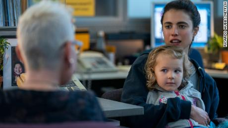 """Margaret Qualley as Alex (far right) holds Rylea Nevaeh Whittet as Maddy in a scene from """"Maid."""""""