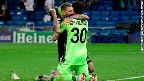 Goalkeeper Giorgos Athanasiadis celebrates with teammate Dimitrios Kolovos at the final whistle.