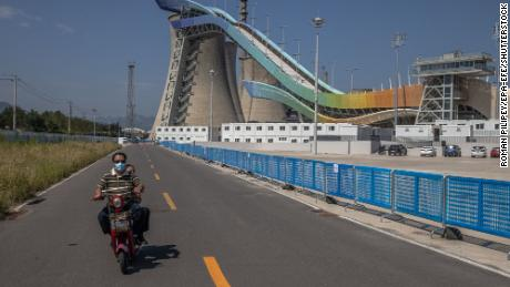 A man rides a scooter next to the Big Air Shougang, a Beijing 2022 site at the site of a former steelworks, in Beijing on September 7.