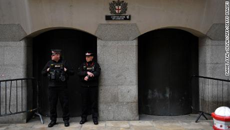 Police officers stand on duty outside the Old Bailey, England's central criminal court, as they await the sentencing of Wayne Couzens for the murder.