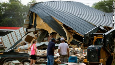 People watch cleanup efforts after buildings were destroyed by flooding in August in Waverly, Tennessee.