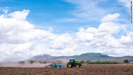 A tractor tears through dry dirt on land that was unplanted this year due to water shortages in Tulelake, California. This summer for the first time, hundreds of farmers along the California-Oregon border who rely on irrigation from Klamath Lake are not getting any water from it.