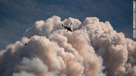 A helicopter carrying a water bucket flies past a pyrocumulus cloud produced by a wildfire burning in the mountains above Lytton, British Columbia, in August.