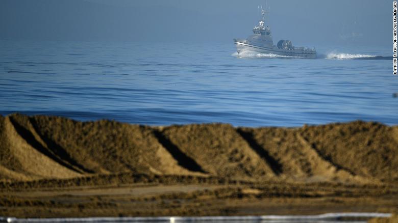 Boats help clean the oil spill near Huntington Beach on Sunday.