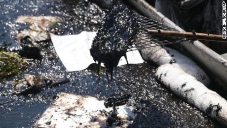 Cleanup contractors deploy skimmers and booms on Sunday, Oct. 3, in Wetlands Talbert Marsh, Huntington Beach, California, to try to stop further infiltration of oil crude.