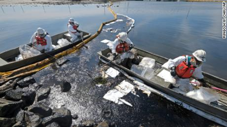 On Sunday, Oct. 3, contractors deploy skimmers and booms to try to get oil into the wetlands Talbert Marsh in Huntington Beach, California.