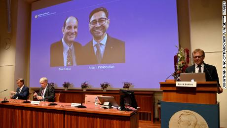 Patrik Ernfors (right), a member of the Nobel Committee for Physiology or Medicine, stands next to a screen displaying the 2021 Nobel Prize winners David Julius and Ardem Patapoutian.