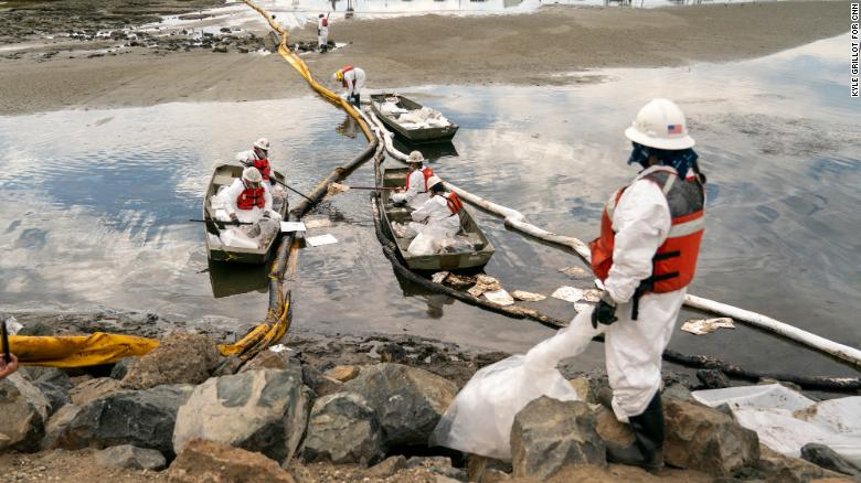 Workers with Patriot Environmental Services clean up some of the oil that flowed into the Talbert Marsh in Huntington Beach, California.