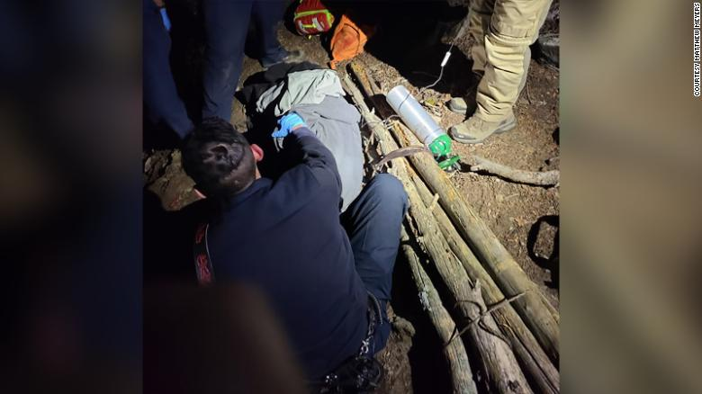 Group of bystanders builds makeshift stretcher to help rescue an injured hiker from a Colorado mountainside