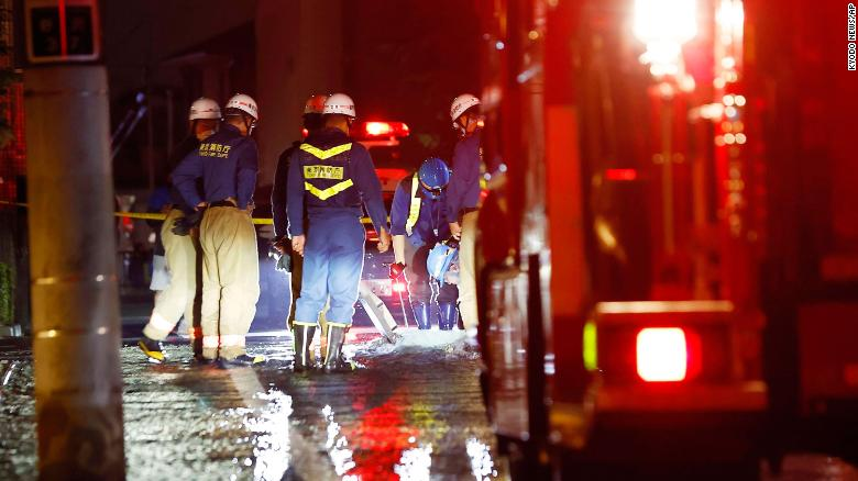 Firefighters work on an inundated road following the quake.