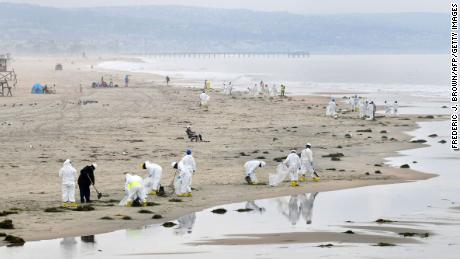 A cleanup crew works on the beach on October 7 in Newport Beach.