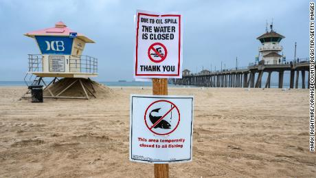 A sign posted in the sand just south of the Huntington Beach Pier lets beach goers know that the shoreline and water are closed due to the offshore oil spill last weekend.