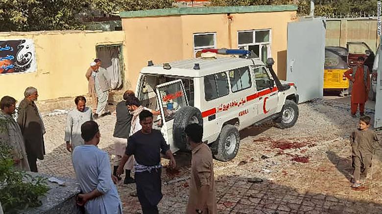 Афганские мужчины стоят рядом с машиной скорой помощи после нападения на шиитскую мечеть в Кундузе.