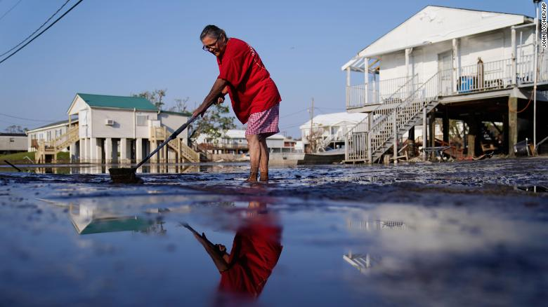 Cindy Rojas cleans mud and floodwater from her driveway in Lafitte, Louisiana, in the aftermath of Hurricane Ida in September.