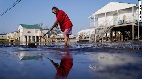 Cindy Rojas cleans mud and floodwater from her driveway in Lafitte, Louisiana, following Hurricane Ida in September.