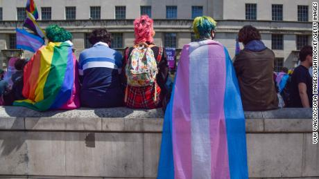 Protesters wrapped in pride and trans pride flags sit on a wall during a trans rights demonstration outside Downing Street.