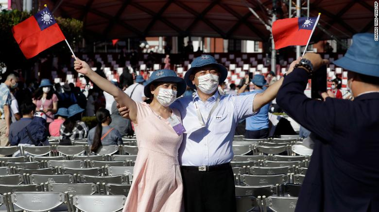 A couple take a photo with Taiwan national flags during National Day celebrations in front of the Presidential Building in Taipei, Taiwan.
