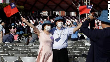 A couple takes a photo with Taiwanese national flags during National Day celebrations outside the Presidential Building in Taipei, Taiwan.