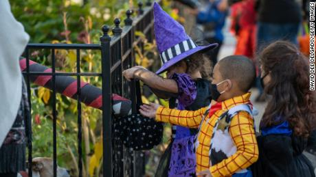 Children receive treats by candy chutes while trick-or-treating for Halloween in Woodlawn Heights on October 31, 2020 in New York City.