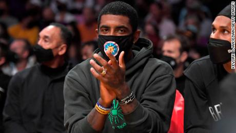 Kyrie Irving cheers from the bench during a preseason game against the Los Angeles Lakers, Oct. 3, 2021, in Los Angeles.
