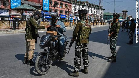 Security personnel check the bag of a motorist along a street in Srinagar on October 9.
