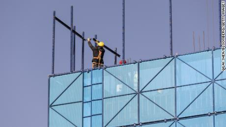 A worker installing safety netting at an apartment block under construction in the Nanchuan area of Xining, Qinghai province, China, on Sept. 28, 2021.