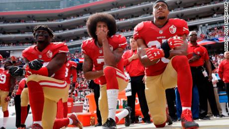 San Francisco 49ers Eli Harold, left, Colin Kaepernick, center, and Eric Reid kneel during the national anthem before the team's game against the Dallas Cowboys.