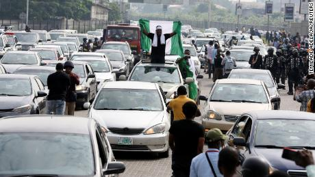 A protester raises a Nigerian flag from a car during a parade of cars to mark the first anniversary of the #EndSARS protest at the Lekki toll booth on Wednesday.