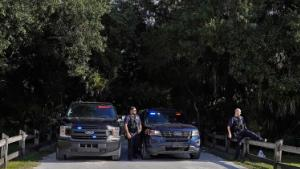 North Port police officers block the entrance to the Myakkahatchee Creek Environmental Park Wednesday, Oct. 20, 2021, in North Port, Fla. Items believed to belong to Brian Laundrie and potential human remains were found in a Florida wilderness park during a search for clues in the slaying of Gabby Petito . (AP Photo/Chris O'Meara)